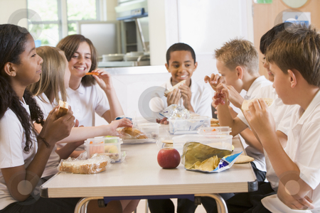 Schoolchildren enjoying their lunch in a school cafeteria stock photo,  by Monkey Business Images