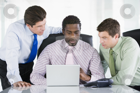 Three businessmen in a boardroom looking at laptop stock photo,  by Monkey Business Images