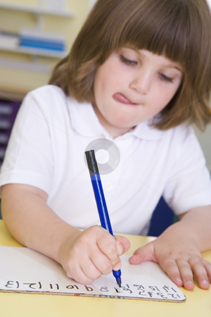 girl learning to write numbers in primary class stock photo by monkey