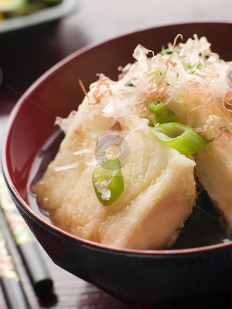 Crisp Fried Tofu in Miso with Bonito Flakes and Pickles stock photo, Dish of Crisp Fried Tofu in Miso with Bonito Flakes and Pickles with chopsticks by Monkey Business Images