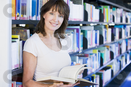 Woman reading in a library stock photo,  by Monkey Business Images