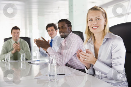 Four businesspeople in a boardroom applauding stock photo,  by Monkey Business Images