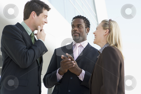 Three businesspeople standing outdoors by building talking and s stock photo,  by Monkey Business Images