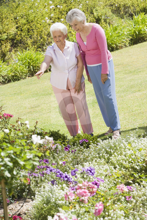 Senior women in garden stock photo, Senior women in garden admiring flowerbeds by Monkey Business Images