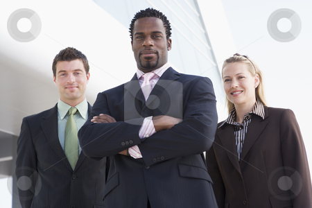 Three business people standing outdoors by building smiling stock photo,  by Monkey Business Images