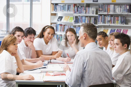 Schoolchildren and teacher studying in school library stock photo,  by Monkey Business Images