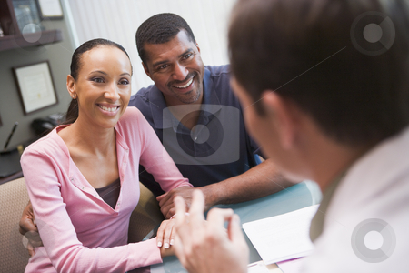 Couple in discussion with doctor in IVF clinic stock photo, Couple in discussion with doctor in IVF clinic sitting at desk by Monkey Business Images