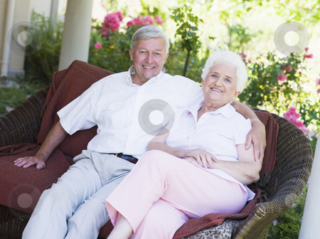 Senior couple relaxing on garden seat stock photo, Senior couple relaxing on garden seat looking to  camera by Monkey Business Images