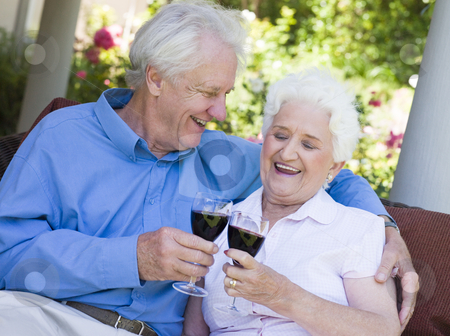Senior couple drinking red wine stock photo, Senior couple celebrating with glass of red wine by Monkey Business Images