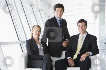 Three businesspeople sitting in office lobby smiling stock photo,  by Monkey Business Images
