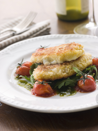 Breadcrumbed Mozzarella Cheese with Roasted Cherry Tomatoes and  stock photo, Plate of Breadcrumbed Mozzarella Cheese with Roasted Cherry Tomatoes and Pesto by Monkey Business Images