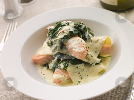 Open Lasagne of Salmon and Spinach with a Saffron Cream stock photo, Plate of Open Lasagne of Salmon and Spinach with a Saffron Cream with cutlery by Monkey Business Images