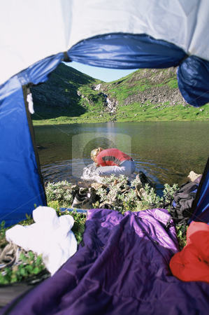 Woman washing face in lake,  view through tent entrance stock photo,  by Monkey Business Images