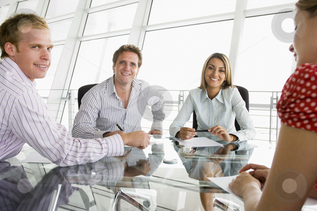 Four businesspeople in a boardroom with paperwork smiling stock photo,  by Monkey Business Images