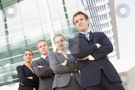 Four businesspeople standing outdoors smiling stock photo,  by Monkey Business Images