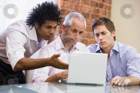 Three businessmen sitting in office with laptop stock photo,  by Monkey Business Images