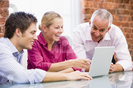 Three businesspeople in office with laptop pointing and laughing stock photo,  by Monkey Business Images