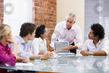 Five businesspeople in boardroom with laptop stock photo,  by Monkey Business Images