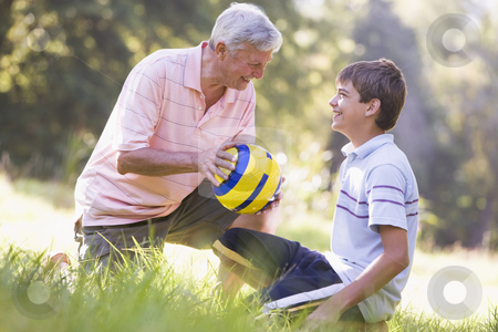Grandfather and grandson at a park with a ball smiling stock photo,  by Monkey Business Images