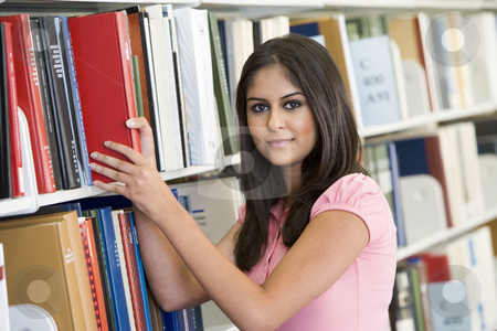 University student selecting book from library stock photo, Female university student selecting book from shelf by Monkey Business Images
