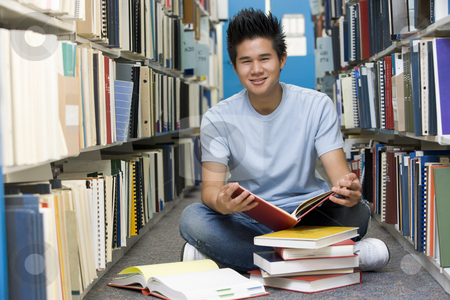 University student working in library stock photo, Male university student sitting on library floor surrounded by books by Monkey Business Images