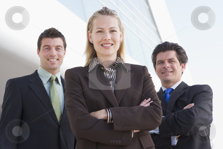 Three businesspeople standing outdoors by building smiling stock photo,  by Monkey Business Images