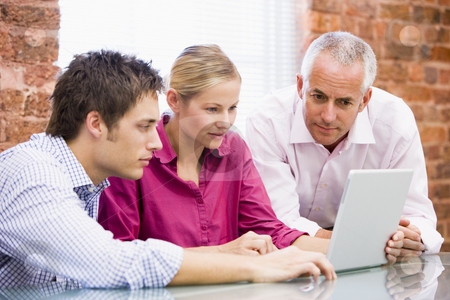 Three businesspeople in office looking at laptop
