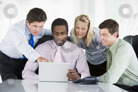 Four businesspeople in a boardroom pointing at laptop and smilin stock photo,  by Monkey Business Images