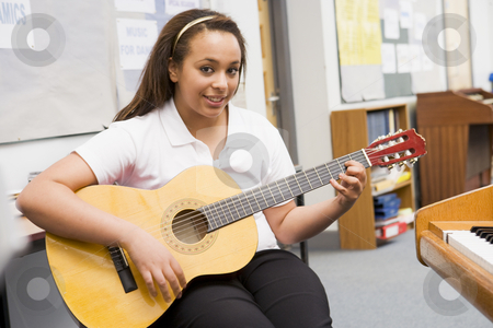 Schoolgirl playing guitar in music class stock photo,  by Monkey Business Images