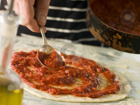 Spooning Tomato sauce onto a Pizza Base stock photo, Man Spooning Tomato sauce onto a Pizza Base by Monkey Business Images