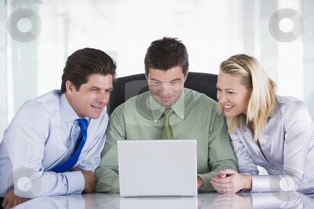 Three businesspeople in office with laptop smiling