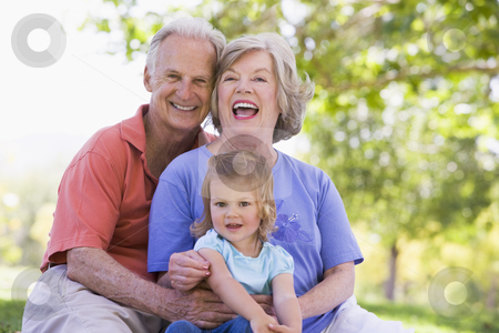 Grandparents with granddaughter in park stock photo,  by Monkey Business Images