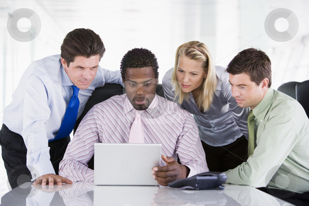 Four businesspeople in a boardroom looking at laptop stock photo,  by Monkey Business Images