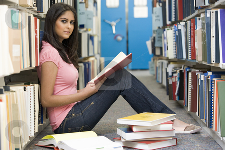 University student studying in library stock photo, Female student sitting on library floor surrounded by books by Monkey Business Images