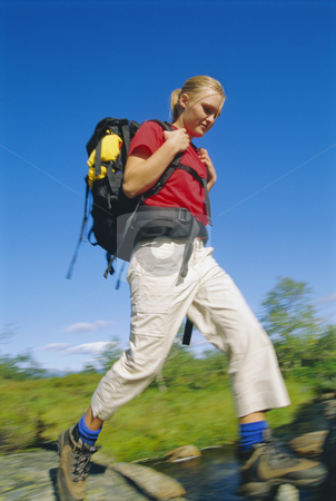 Young woman wearing backpack stepping across river stock photo,  by Monkey Business Images