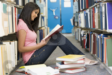University student working in library stock photo, Female student sitting on library floor surrounded by books by Monkey Business Images