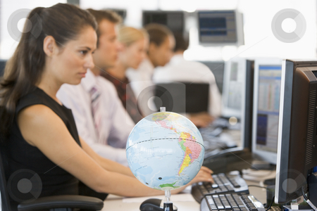 Five businesspeople in office space with desk globe in foregroun