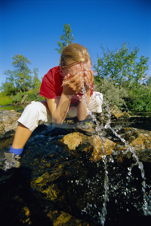 Young woman washing her face in river stock photo,  by Monkey Business Images