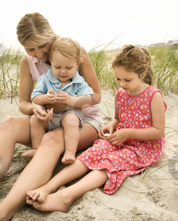 Mother and children looking at shells. stock photo, Caucasian mid-adult woman sitting with male toddler on lap and beside Caucasian female child on beach  looking at shells. by Iofoto Images