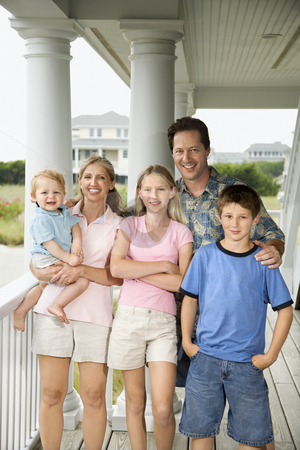 Family portrait. stock photo, Family portrait of Caucasian mid-adult man and woman with pre-teen girl and boy and male toddler, standing on porch. by Iofoto Images