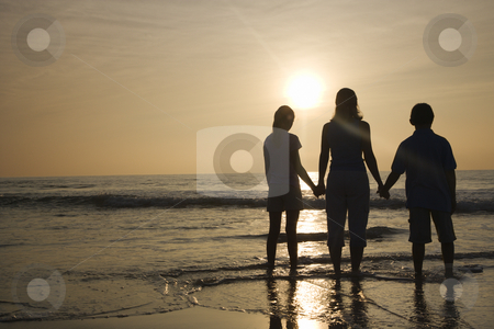 Mom and kids at beach. stock photo, Caucasian mid-adult mother and tenage kids standing silhouetted on beach at sunset. by Iofoto Images