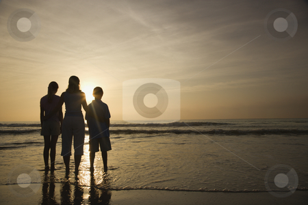 Family at beach. stock photo, Caucasian mid-adult mother and teenage kids standing silhouetted on beach at sunset. by Iofoto Images