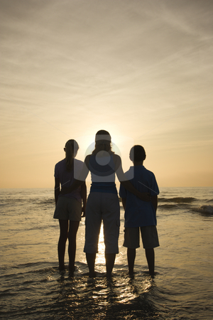 Mom and kids at beach. stock photo, Caucasian mid-adult mother and teenage kids standing silhouetted on beach at sunset. by Iofoto Images