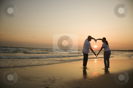 Couple in love. stock photo, Mid-adult couple making heart shape with arms on beach at sunset. by Iofoto Images