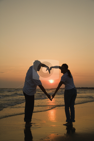Romantic couple. stock photo, Mid-adult couple making heart shape with arms on beach at sunset. by Iofoto Images