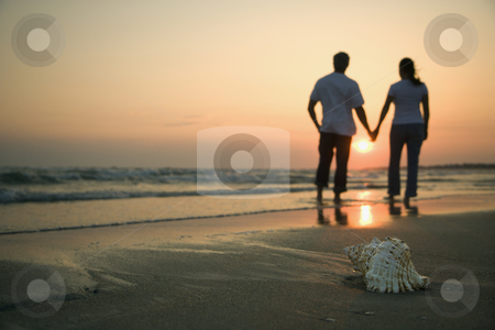 Couple holding hands. stock photo, Back view of mid-adult couple holding hands walking on beach with seashell in foreground. by Iofoto Images