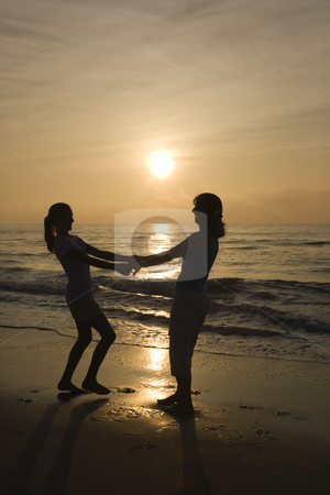 Mom and daughter on beach. stock photo, Caucasian mid-adult mother and teenage daughter holding hands spinngin on beach at sunset. by Iofoto Images