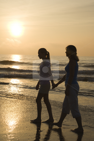 Mom and daughter at sunrise. stock photo, Caucasian prime adult female and female child walking on beach at sunset holding hands. by Iofoto Images