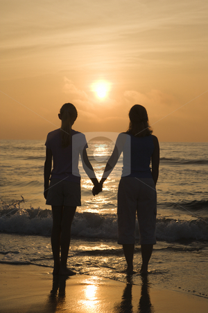 Mom and daughter at sunrise. stock photo, Caucasian mid- female and teenage daughter standing on beach at sunset holding hands. by Iofoto Images