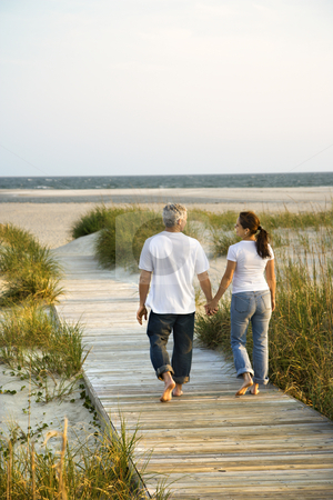 Couple at beach. stock photo, Back view of mid-adult Caucasian couple walking down walkway to beach. by Iofoto Images
